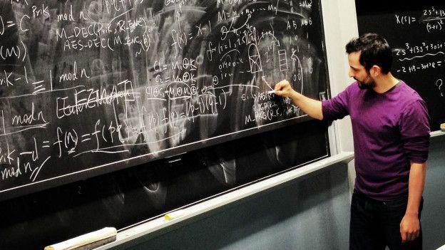 Un hombre escribe fórmulas matemáticas en una pizarra