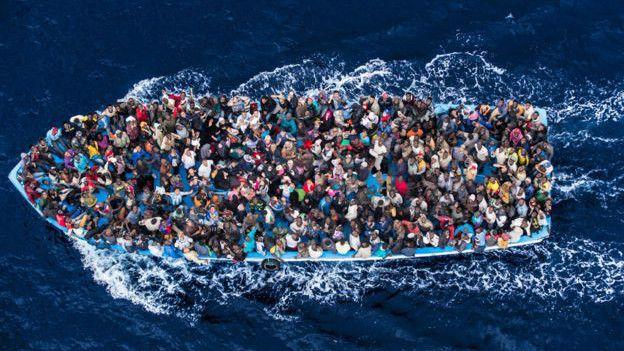Imagen de inmigrantes en una barca en el mar entre Libia e Italia