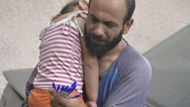 Un inmigrante ofrece en bolígrafos en venta mientras carga a su hija