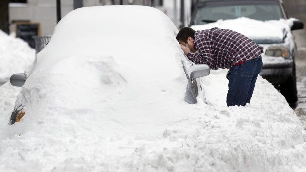 Un hombre y un carro cubierto de nieve