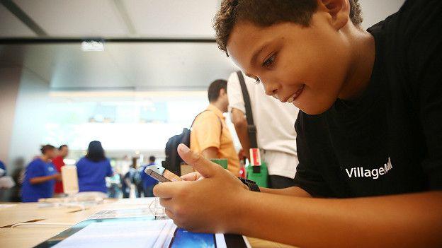 Un niño mira la pantalla de un celular
