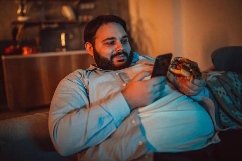 Un hombre obeso mirando su celular mientras come una hamburguesa