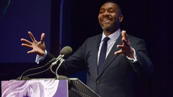 Lenny Henry stands at a lectern with his arms outstretched smiling