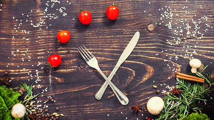 A knife and fork look like a clock with mushrooms and tomatoes being the digits on the clock