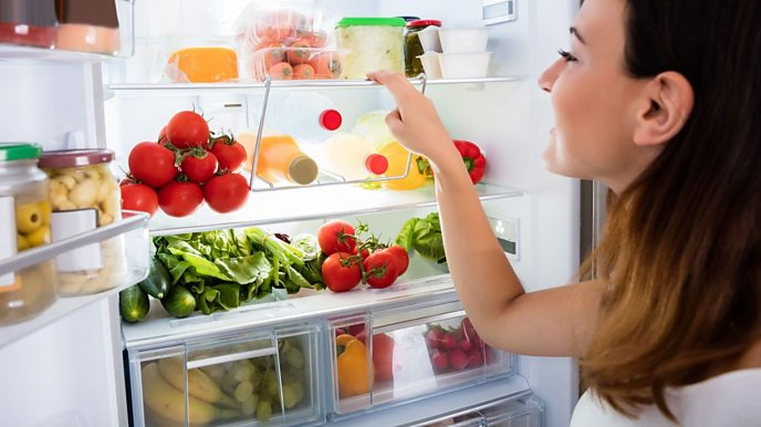 Woman looking in fridge with lots of fruit and vegetables.