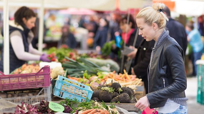Woman at a market buying fruit and veg