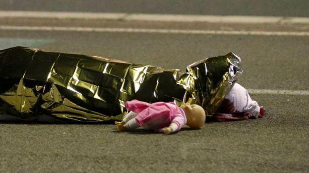 Essa imagem de uma boneca ao lado de um corpo já se tornou um símbolo do ataque