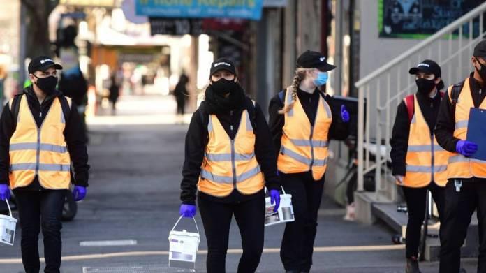Cleaners wearing masks walk along Elizabeth Street in Melbourne, Australia, 03 Septemberr 2020.