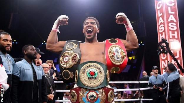 Anthony Joshua celebrates with his belts in the ring after beating Andy Ruiz Jr.