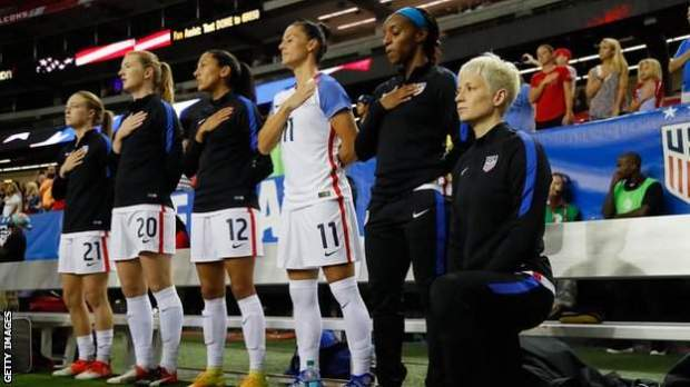 US women's soccer star Megan Rapinoe (right) kneels while team-mates stand during the playing of the national anthem prior to a match