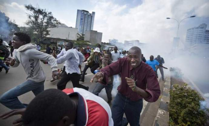Opposition supporters, some carrying rocks, flee from clouds of tear gas fired by riot police, during a protest in downtown Nairobi, Kenya Monday, May 16, 2016.