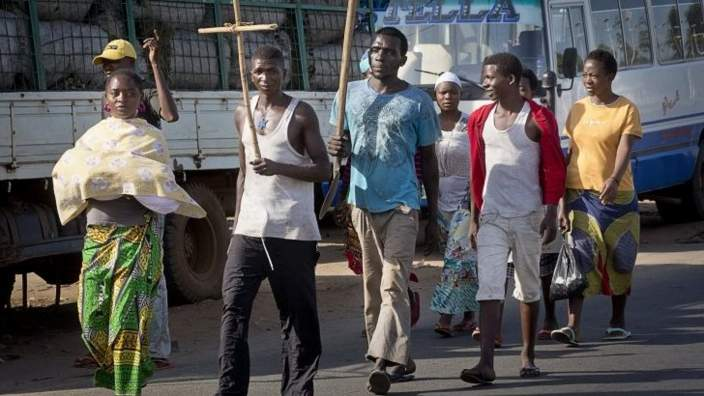 A civilian carries a Christian cross as a sign of impartiality as he and others walk down a major road in the capital Bujumbura, in Burundi Thursday, 14 May 2015
