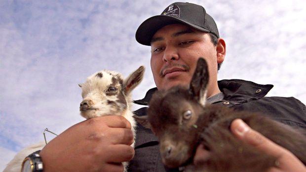 Brandon Billie holding some kid goats