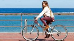 A girl rides her bike at promenade of Las Canteras beach after restrictions were partially lifted for children for the first time in six weeks