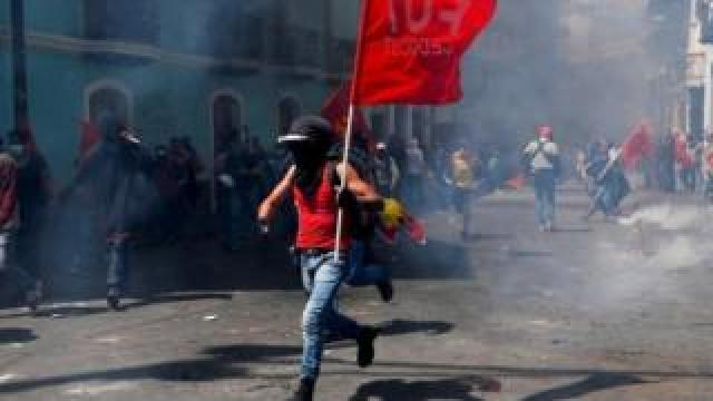 Protester running through the streets waving a red flag