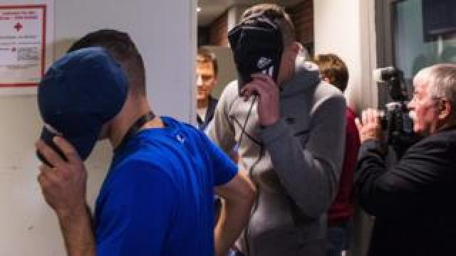 Two of six young men accused of setting fire to a sleeping homeless man hide their faces as they arrive for their trial at court in Berlin, 13 June 2017