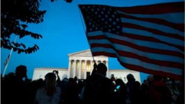 A person holds a US National flag outside of the US Supreme Court