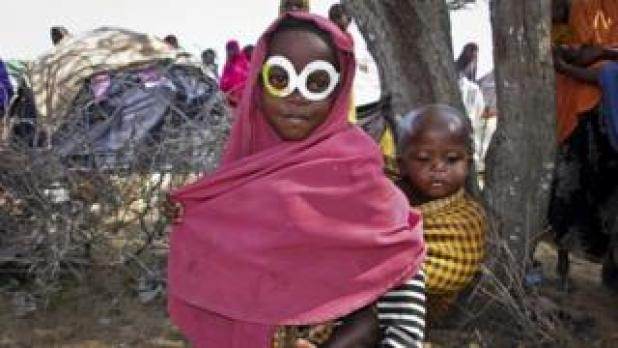 A young Somali girl who was displaced by the drought wears a pair of mock spectacles cut out from a cardboard box of antibiotics medicine as a joke, as she carries her brother around a camp just outside of Mogadishu, in Somalia Tuesday, March 28, 2017