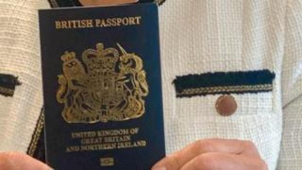 Home Secretary Priti Patel holding a blue passport