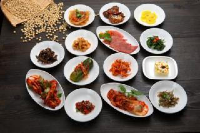 A table with lots of small Korean dishes