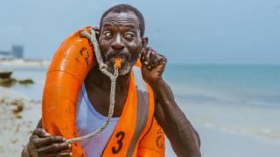 Lifeguard Nicholas Paul whistling on the beach in Lagos, Nigeria