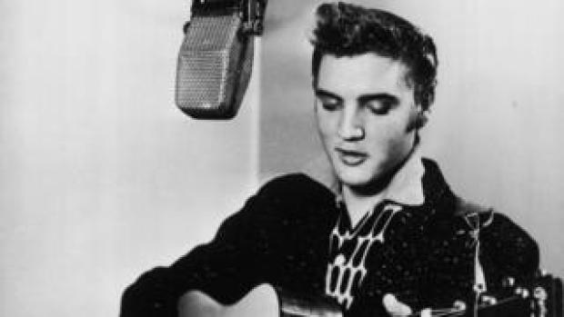 Elvis Presley pictured in a recording booth, playing a guitar