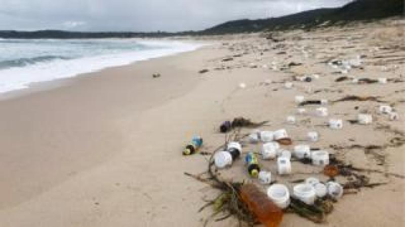 Small plastic containers litter beach near Port Stephens in New South Wales