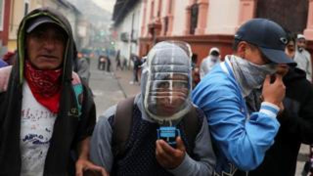 A protester uses a plastic bottle as a gas mask