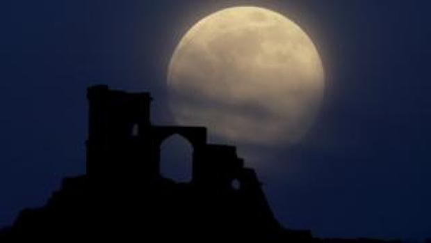 The supermoon rises over Mow Cop in Staffordshire