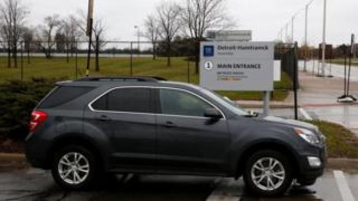 A car drives by the General Motors Detroit-Hamtramck Assembly, one of the plants where GM will stop production