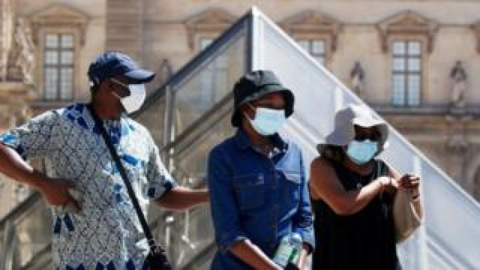 People wearing protective masks walk near the Louvre Museum in Paris