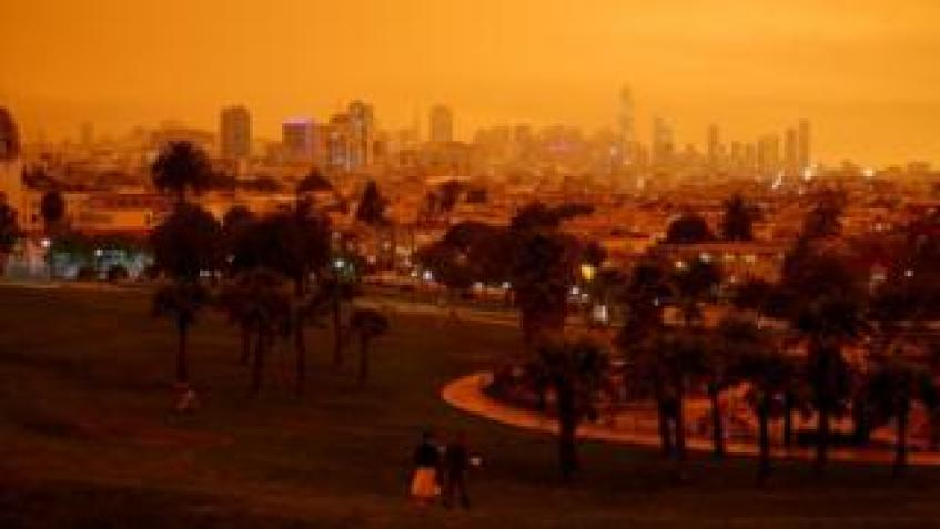 Downtown San Francisco is seen from Dolores Park under an orange sky