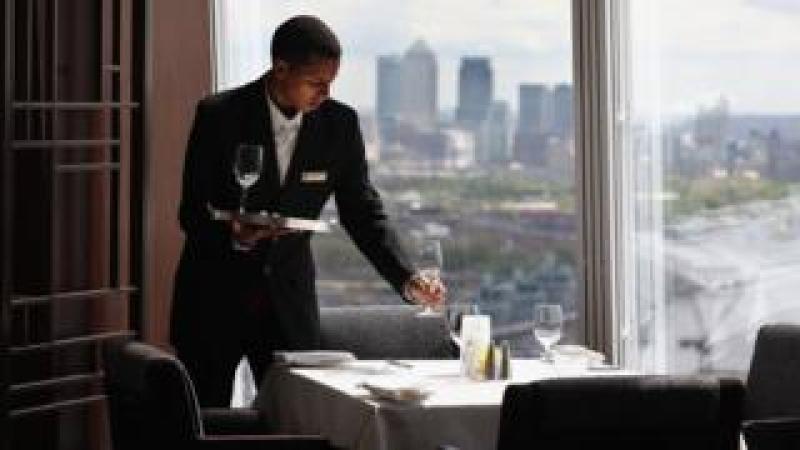 A waiter prepares a table