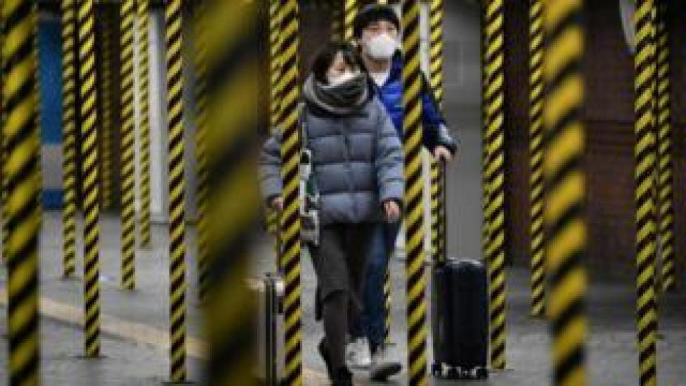 Passengers wearing face masks walk between columns at a subway station being renovated in Seoul