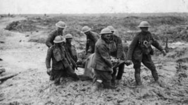 A stretcher-bearing party carrying a wounded soldier through the mud near Boesinghe during the battle of Passchendaele in Flanders