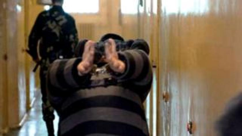 Un prisionero camina doblado viendo hacia abajo y con las manos esposadas en una prisión bielorrusa en 2006.