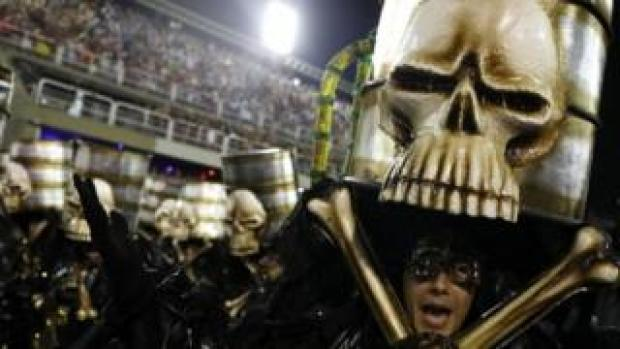Skull-shaped oil barrels are lifted up at Rio Carnival
