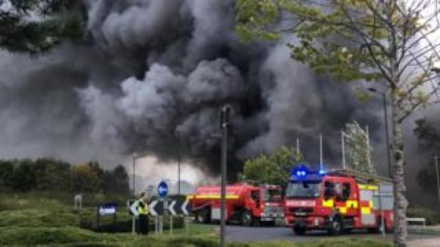 A photo shows plumes of black smoke coming from the building