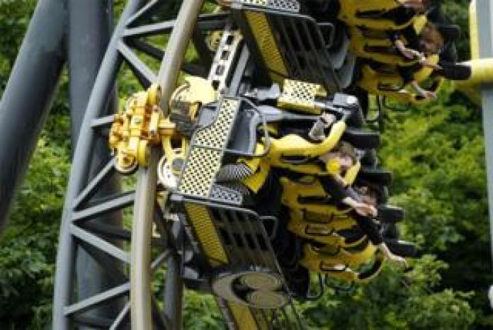 People ride a roller coaster