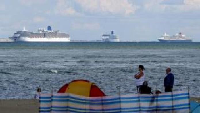People on Studland Beach watch the cruise ships