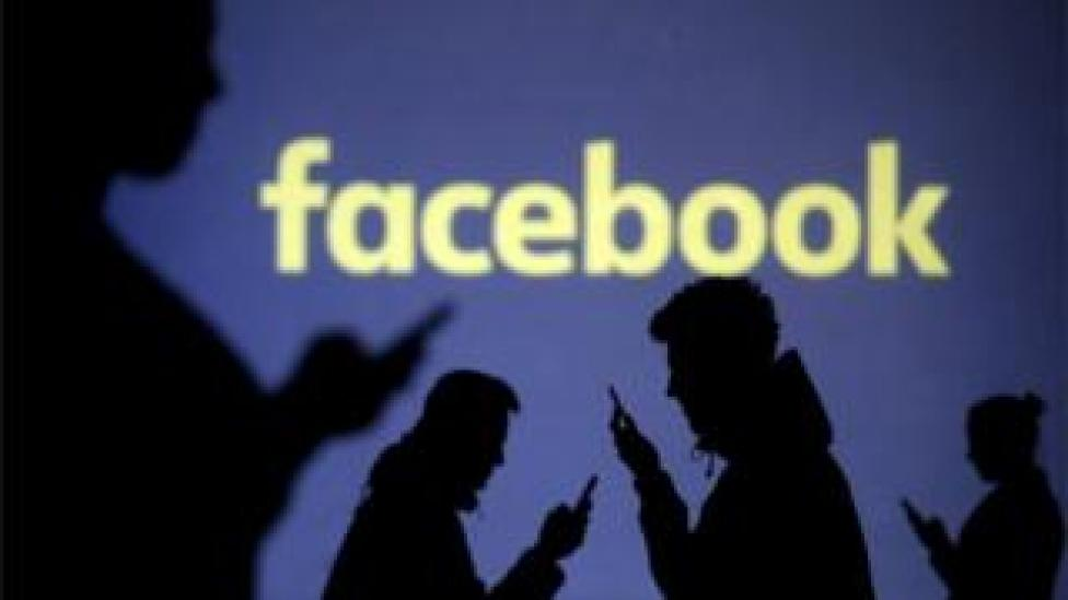 Smartphone users silhouetted against the Facebook logo (file photo)