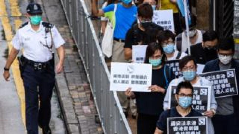 Pro-democracy protesters hold black placards as they march on the Chinese Liaison Office in Hong Kong