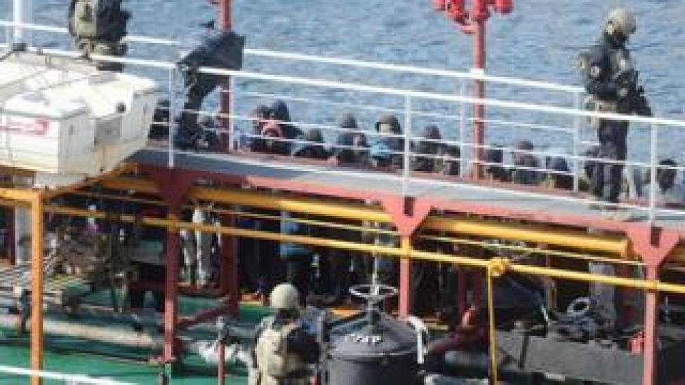 Maltese forces and migrants stand onboard El Hiblu 1, which was allegedly hijacked by migrants it had rescued off the coast of Libya