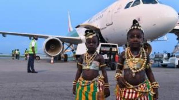Two young girls in traditional dress pose in front of the tenth airplane of Ivory Coast's national carrier Air Cote d