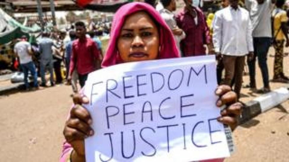 A Sudanese protestor holds a placard which reads 'Freedom Peace Justice' during a protest outside the army complex in the capital Khartoum on 18 April 2019.