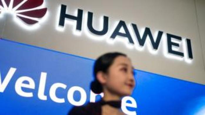 A hostess welcomes journalists and guests who attend the Huawei database and storage product launch during a press conference at the Huawei Beijing Executive Briefing Centre in Beijing on May 15, 2019.