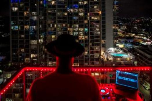 A music DJ stands on a balcony and performs to surrounding flats