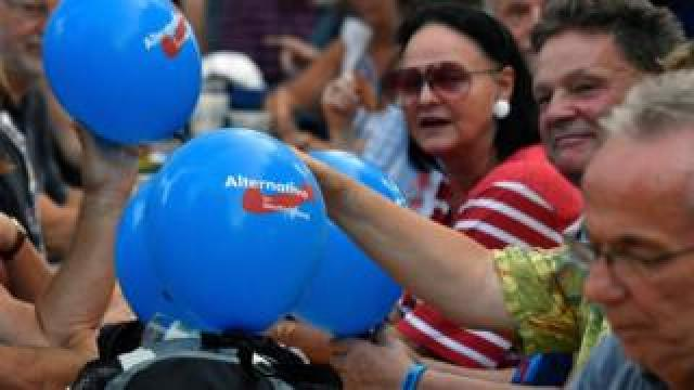 People with balloons attend an election rally of the far-right party Alternative for Germany (AfD) in Koenigs Wusterhausen