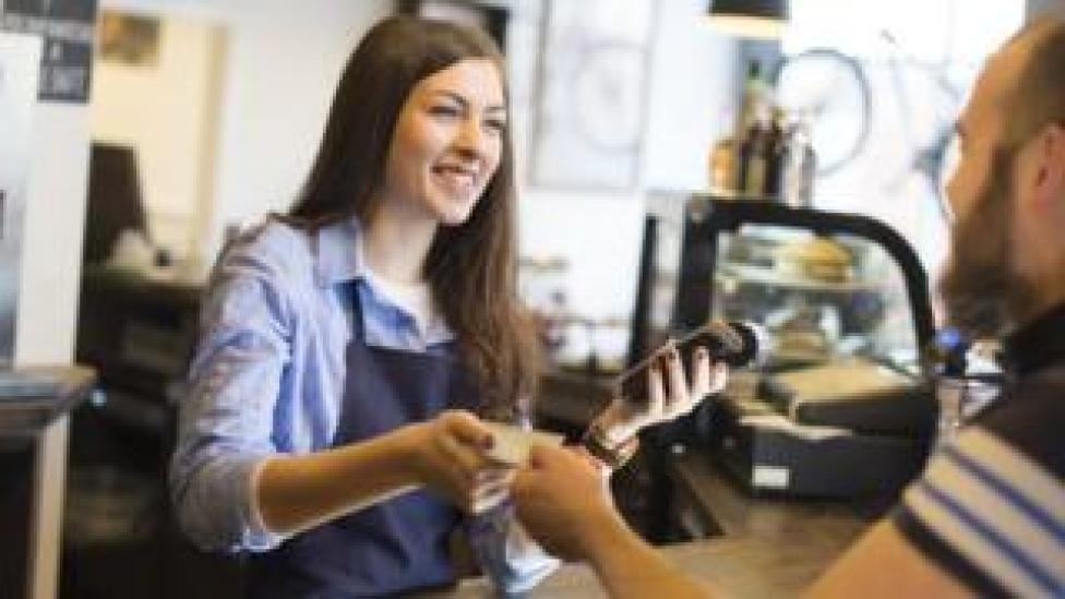 Waitress taking payment at till