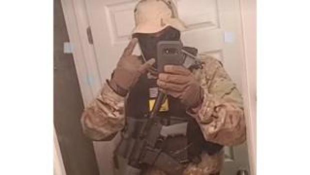 Screengrab showing a man with an assault rifle making a TikTok video